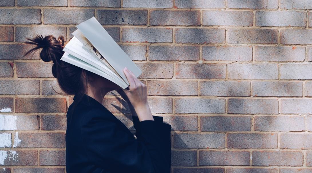 英語学習に行き詰まり、教科書に顔をうずめる女学生